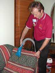 Michael Carmody cleaning the upholstery on a lounge suite